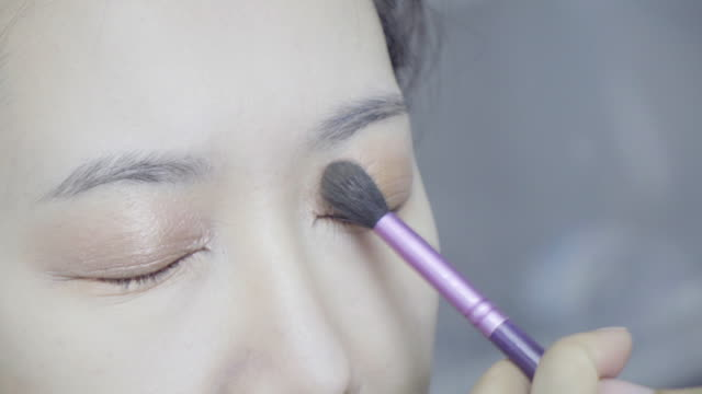 Professional-make-up-artist-making-up-her-model-face