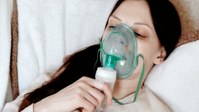 Use-nebulizer-and-inhaler-for-the-treatment-Young-woman-inhaling-through-inhaler-mask-lying-on-the-couch-Side-view-