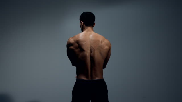 Male-Fitness-Model-Displays-Back-Muscles-by-Performing-Stretch-Exercises