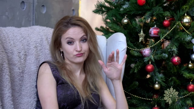 Young-woman-shaking-head-to-reject-no-on-christmas-tree-background