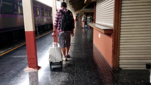 Los-turistas-a-pie-arrastre-equipaje-en-la-estación-de-tren-Concepto-de-trabajo-y-viajes-
