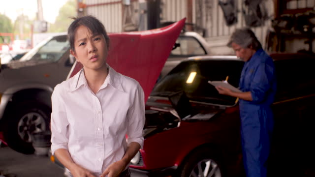 Portrait-of-angry-customer-while-a-mechanic-works-on-a-car-in-the-background-car-service-concept
