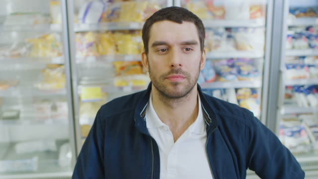 Portrait-Shot-of-the-Handsome-Man-Choosing-Tin-Can-from-the-Canned-Goods-Section-and-Places-it-In-His-Shopping-Cart-In-the-Background-Frozen-Goods-Section-of-the-Store-