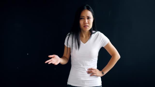 Porträt-von-wütenden-asiatische-Frau-sprechen-und-Gestikulieren-negative-Gefühle-zeigen-vor-schwarzem-Hintergrund-stehen-Junge-Menschen-Negativität-und-Wut-Konzept-