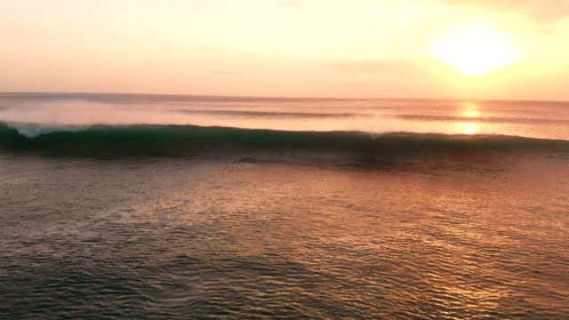 Aerial-view-with-ocean-and-waves-at-warm-sunset-in-Bali