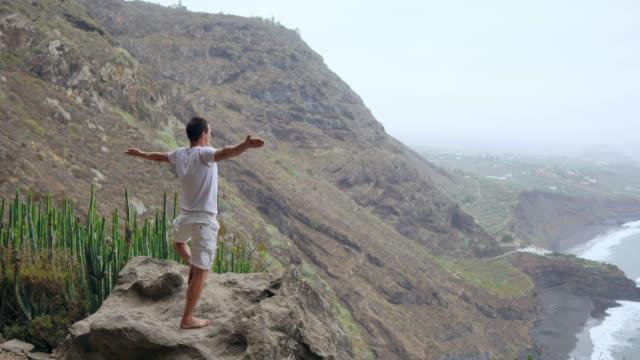 Fit-junger-Mann-praktiziert-Sonne-Anrede-Yoga-in-den-Bergen-für-Ozean-Junger-Mann-genießen-Meditation-und-Yoga-Fitness-Sport-People--und-Lifestyle-Konzept---junger-Mann-der-Yoga-Übungen