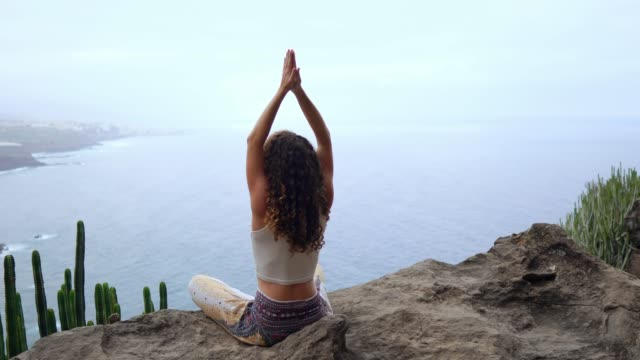 Woman-meditating-on-top-of-a-rock-at-the-mountains-at-sunrise-Practice-yoga-on-outdoor-