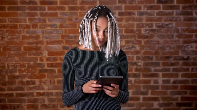 Young-African-girl-with-dreadlocks-using-a-tablet-computer-looking-at-the-camera-and-smiling-Brick-wall-in-the-background-