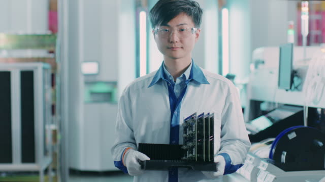 On-High-Tech-Factory-Asian-Worker-Holds-Batch-with-Electronic-Printed-Circuit-Board-Assembled-with-use-of-Surface-Mount-Technology-on-Pick-and-Place-Machinery-