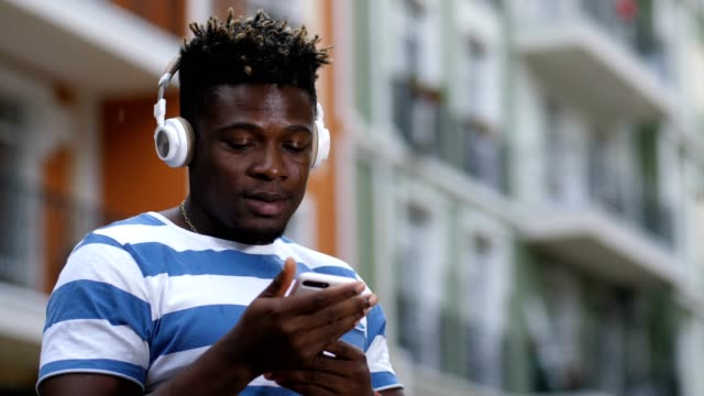 Hipster-man-in-headset-choosing-music-on-cellphone