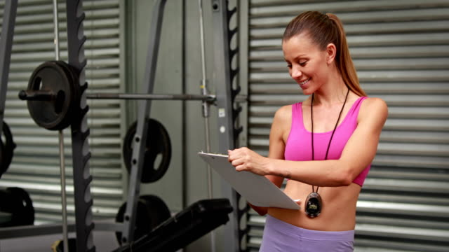 Trainer-taking-notes-at-gym-gym