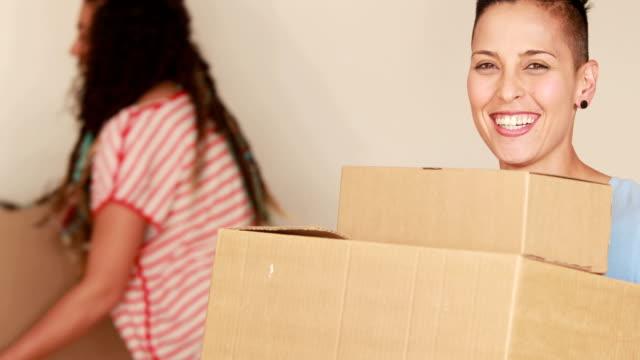 Smiling-lesbian-couple-moving-boxes