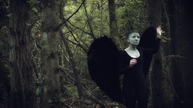 4k-Halloween-mujer-oscura-de-Angel-negro-alas-en-bosque-buscando-y-buscando