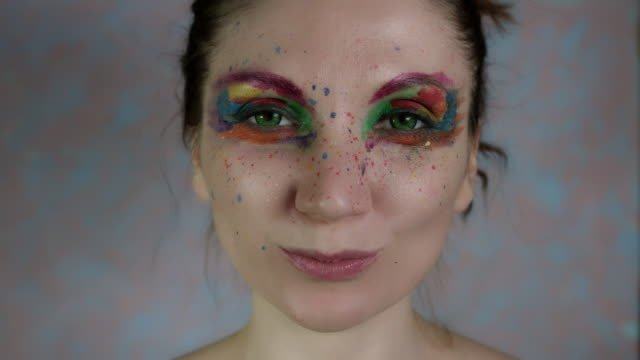 4k-Shot-of-a-Woman-with-Multicoloured-Make-up-Eating-Carrot