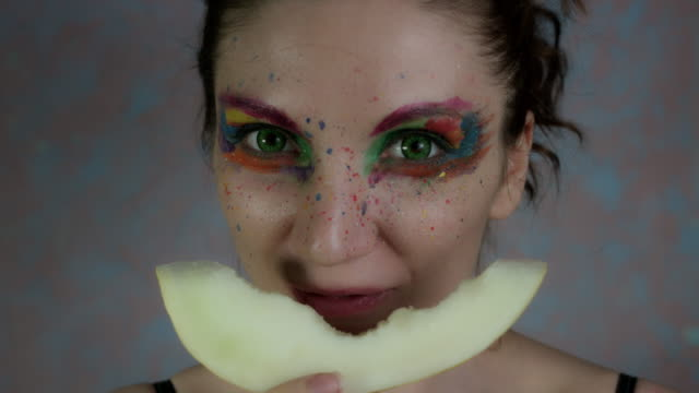 4k-Shot-of-a-Woman-with-Multicoloured-Make-up-eating-Melon