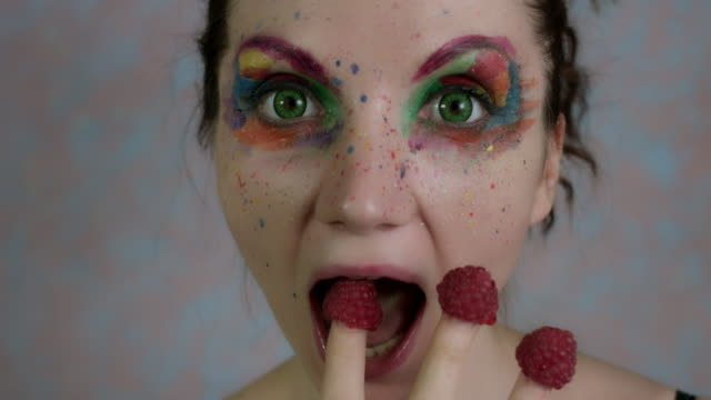 4k-Shot-of-a-Woman-with-Multicoloured-Make-up-Eating-Raspberry
