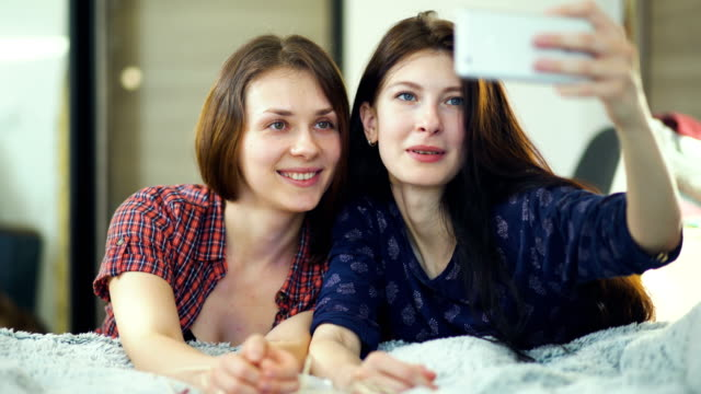 Two-happy-women-friends-lying-in-bed-and-making-selfie-in-morning-and-have-fun-on-bed