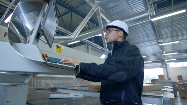 Engineer-Wearing-Hard-Hat-Setting-Up-CNC-Machine-at-the-Factory