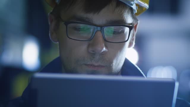 Técnico-en-gafas-y-casco-con-tableta-en-el-ambiente-Industrial-Reflexiones-de-gafas-de-pantalla