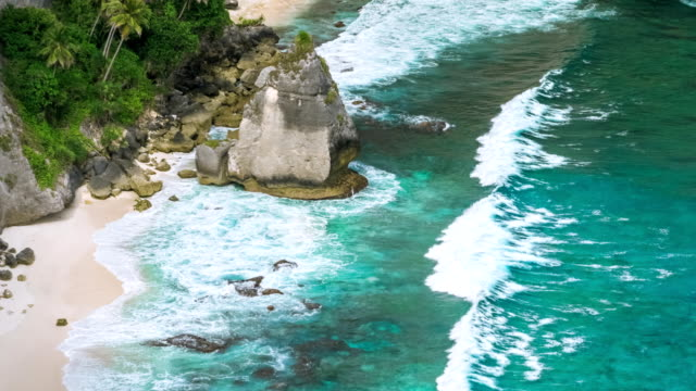 Rock-in-the-ocean-with-beautiful-palms-behind-at-Atuh-beach-on-Nusa-Penida-island-Indonesia