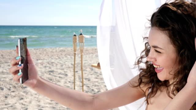 Fotos-de-vacaciones-niña-sonriente-en-el-mar-de-fondo-y-arena-mujer-en-la-costa-del-océano-resto-de-verano-el-viento-desarrolla-pelo