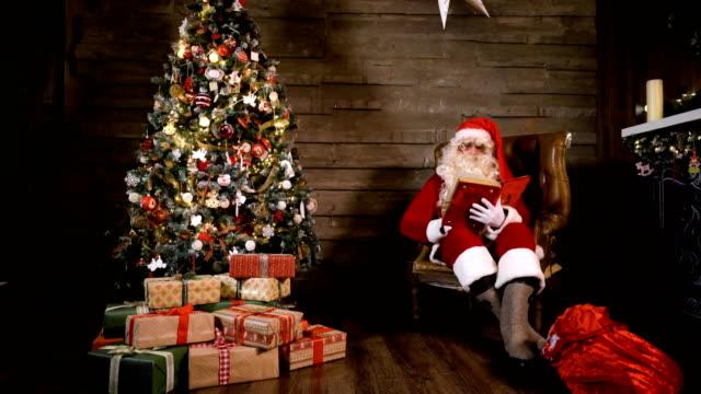 Santa-Claus-Read-Book-near-X-mas-Tree