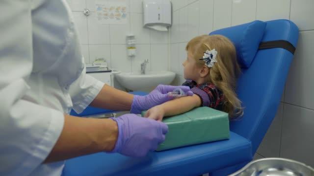 Enfermera-es-tomar-muestra-de-sangre-de-una-vena-en-el-brazo-de-la-niña