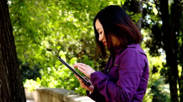 China-joven-mujer-utilizando-Digital-Tablet-y-sonriente-al-aire-libre