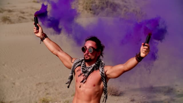 Young-man-with-smoke-bombs-celebrating-at-desert-music-festival