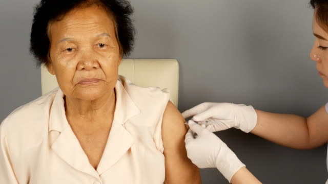 Doctor-injecting-flu-vaccine-to-patient-s-arm-in-local-hospital