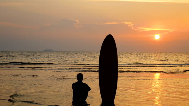 4K-silhouette-of-surfer-man-sitting-on-the-sea-beach-with-long-surf-boards-at-sunset-on-tropical-beach