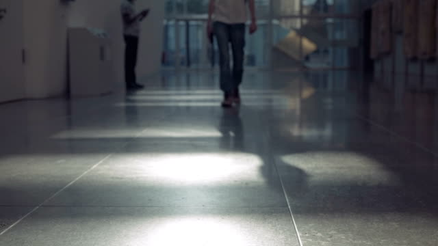 male-legs-in-jeans-move-to-the-camera-along-the-corridor-with-artificial-lighting