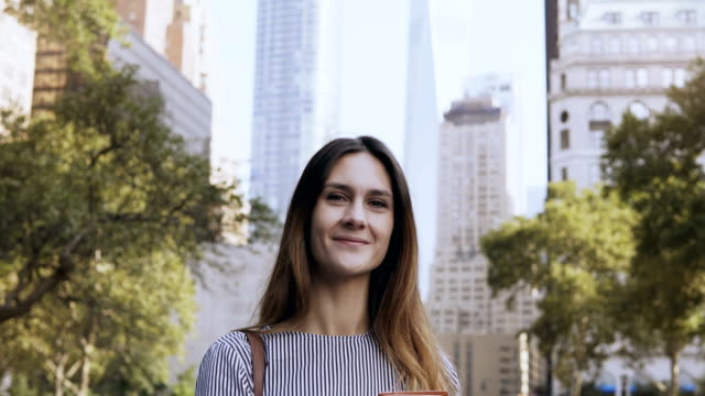 Portrait-of-young-happy-businesswoman-standing-in-the-park-of-financial-centre-of-New-York-USA-and-holding-documents