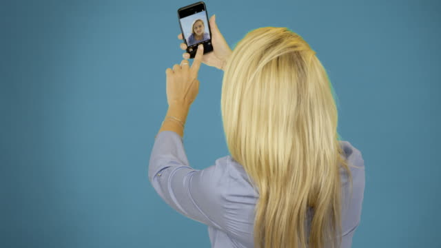beautiful-woman-taking-selfie-using-phone-on-blue-background-Smiling-and-spinning-enjoying-lifestyle-concept-