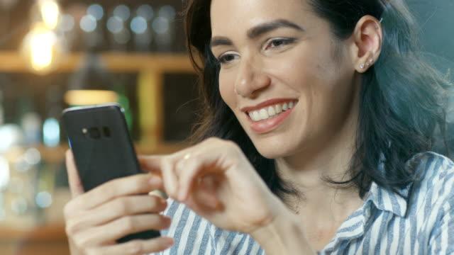 Close-up-retrato-toma-de-una-bella-joven-sonriente-y-el-uso-de-teléfono-móvil-En-el-fondo-café-con-estilo-