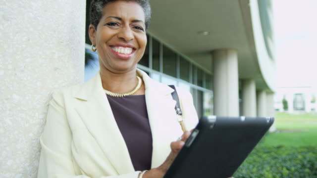 Portrait-of-African-American-female-lecturer-holding-touchscreen