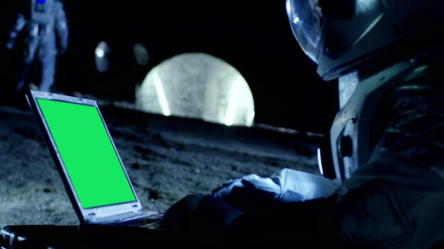 Astronauta-del-planeta-extranjero-trabaja-en-un-portátil-con-pantalla-verde-de-maqueta-En-el-fondo-su-miembro-de-la-tripulación-y-los-Habitat-del-espacio-Concepto-de-colonización-extraterrestre-