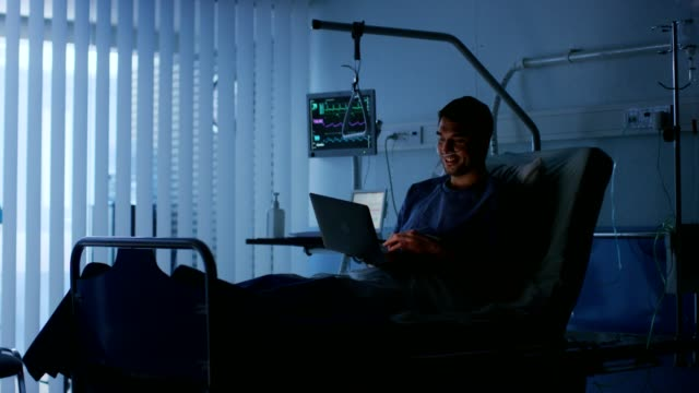 En-el-Hospital-recuperación-de-hombre-paciente-utiliza-Laptop-mientras-la-mentira-en-la-cama-Usando-la-tecnología-para-comunicarse-con-los-seres-queridos-