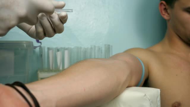 Hombre-mano-de-médico-inyecta-una-jeringa-en-la-vena-del-paciente-Brazo-de-medic-que-vacuna-inyección-al-enfermo-en-el-hospital-Vista-de-cerca