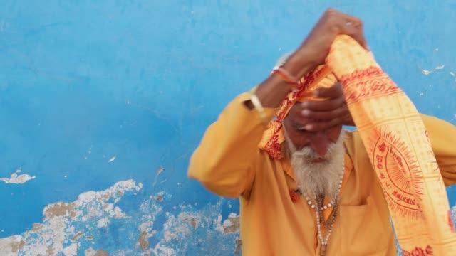 Indian-sadhu-saffron-holy-clothes-putting-on-a-turban-against-a-blue-wall