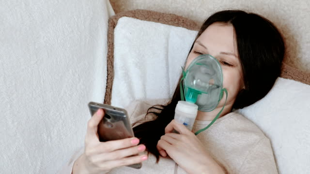 Use-nebulizer-and-inhaler-for-the-treatment-Young-woman-inhaling-through-inhaler-mask-lying-on-the-couch-and-chatting-in-mobile-phone-Side-view-