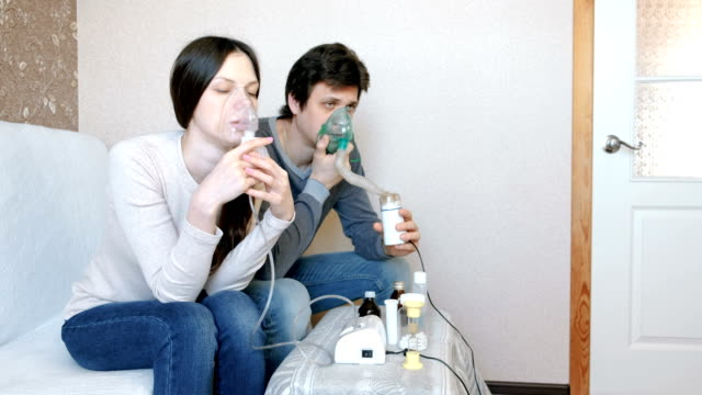 Use-nebulizer-and-inhaler-for-the-treatment-Man-and-woman-inhaling-through-inhaler-mask-Front-view-