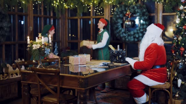 Santa-Claus-is-writing-a-letter-on-the-typewriter-and-watching-as-the-Elves-are-throwing-each-other-presents-on-the-background-of-Christmas-decorations-in-the-room-on-the-eve-of-the-New-Year