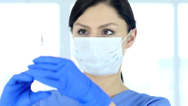 Close-Up-of-Doctor-in-Mask-Holding-Injection-Ready-to-inject