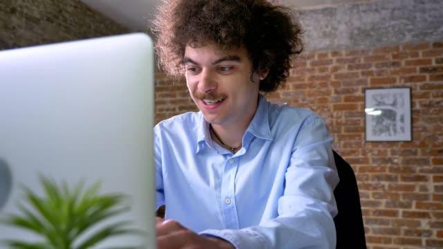 Divertida-oficinista-joven-con-pelo-rizado-escribiendo-en-la-laptop-y-sentado-a-la-mesa-en-la-oficina-moderna-sonriendo