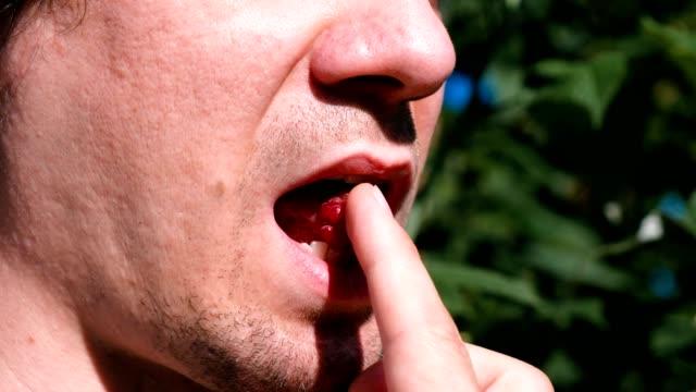 Man-eats-raspberries-mouth-close-up-