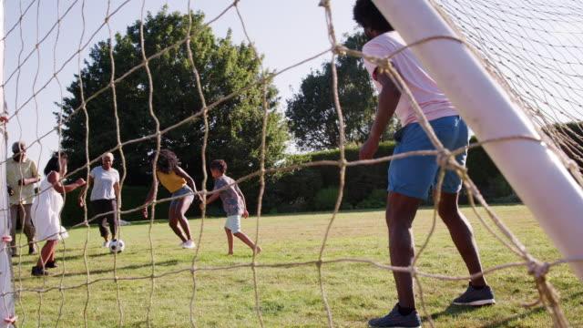 Multi-familia-de-generación-negro-jugando-al-fútbol-en-el-jardín