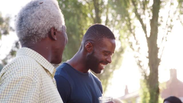 Abuelo-habla-con-sus-hijos-y-su-nieto-en-barbacoa-familiar