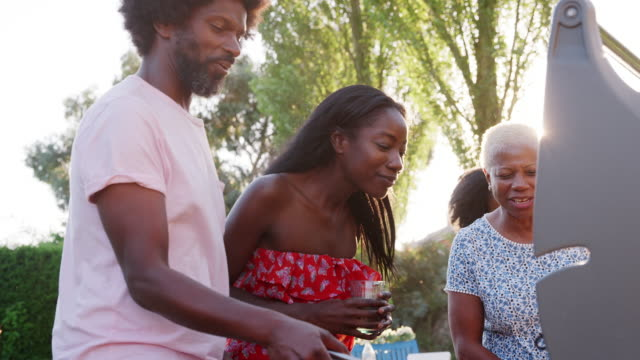 Couple-talking-at-multi-generation-family-barbecue