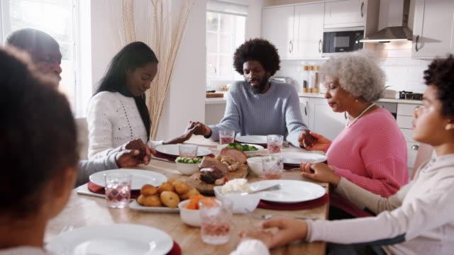 Multi-Generation-die-gemischte-Rennen-Familie-Hand-in-Hand-und-sagt-Gnade-am-Tisch-vor-dem-Essen-ihre-Sonntagsessen-selektiven-Fokus